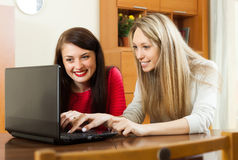 Happy women at table with laptop Stock Photos