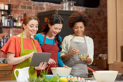 Happy women with tablet pc cooking in kitchen Stock Images