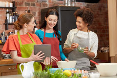 Happy women with tablet pc cooking in kitchen Royalty Free Stock Image