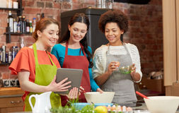 Happy women with tablet pc cooking in kitchen Royalty Free Stock Photos