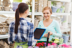 Happy women with tablet pc at flower shop Royalty Free Stock Image
