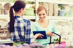 Happy women with tablet pc at flower shop Stock Photos