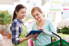 Happy women with tablet pc in greenhouse Royalty Free Stock Photography