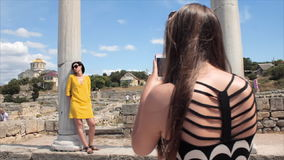 Happy women taking photo girl friend with smartphone on the ruins of the ancient city background stock video
