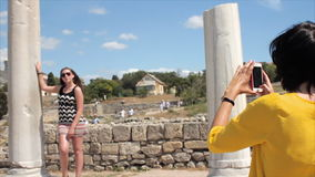 Happy women taking photo girl friend with smartphone on the ruins of the ancient city background stock footage