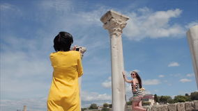 Happy women taking photo girl friend with smartphone on the ruins of the ancient city background stock video footage