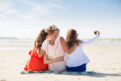 Happy women taking selfie by smartphone on beach. Summer vacation, holidays, travel, technology and people concept- group of smiling young women taking selfie royalty free stock image