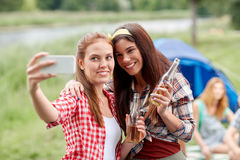 Happy women taking selfie by smartphone at camping Stock Images
