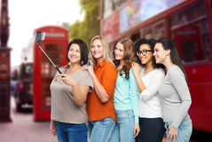 Happy women taking selfie by smartphone in london. Friendship, technology, travel, tourism and people concept - group of happy different women taking picture Stock Photos