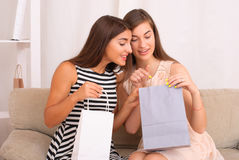 Happy women together looking purchases from shopping bags Royalty Free Stock Photos