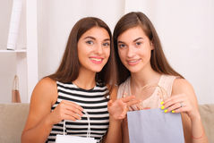 Happy women together looking purchases from shopping bags Stock Photo