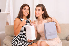 Happy women together looking purchases from shopping bags Stock Photography