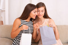 Happy women together looking purchases from shopping bags Royalty Free Stock Images