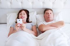 Happy woman and unhappy man in bedroom, middle age couple, family problem stock photography