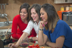Happy women using laptop together in the kitchen. Royalty Free Stock Photography
