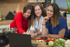 Happy women using laptop together in the kitchen. Royalty Free Stock Photo