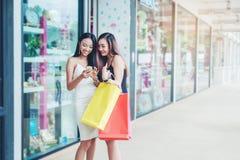 Happy women using phone Enjoying Spending shopping bags in Fashi Stock Photos