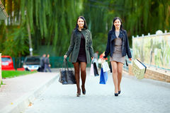 Happy women walk the city with shopping bags Stock Photo
