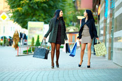 Happy women walk the city with shopping bags Royalty Free Stock Photo