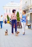 Happy women walking the dogs on city street. Happy women walking with the dogs on city street royalty free stock image