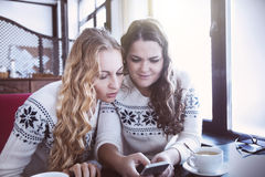 Happy women watching to the mobile phone in a cafe Stock Image