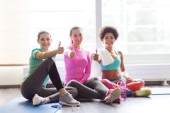 Happy women with water showing thumbs up in gym Royalty Free Stock Images