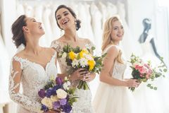 Happy women in wedding dresses with flowers royalty free stock photos