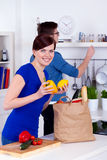 Happy woman and young man unpacking groceries Royalty Free Stock Image