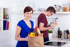 Happy woman and young man unpacking groceries Stock Photos