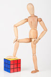 Happy wood mannequin stand next to cube puzzle confused after so Royalty Free Stock Photography