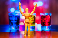 Happy wooden dummy, mannequin or man figurine. Silhouette stand against the backdrop of alcohol drinks. Friday background Royalty Free Stock Photography
