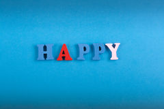 HAPPY word on blue background composed from colorful abc alphabet block wooden letters, copy space for ad text. Learning. Word on blue background composed from stock image