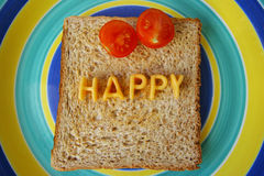 Happy word on toast. The word happy made from alphabetti spaghetti on a piece of toast stock photography