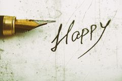 `Happy` word written on white paper using ink pen. Vintage style Stock Photo