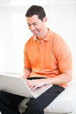 Happy work at home male working on laptop smiling.  Stock Photography