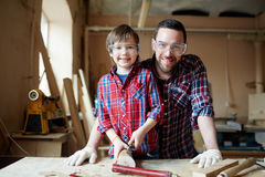 Happy work. Man and boy in protective eyewear carving wooden planks in workshop Stock Image