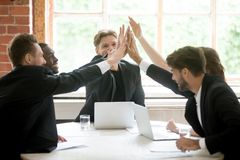 Happy work team giving high five after closing business deal. Multiracial work team giving high five happy after successful business deal at briefing. Managers stock photography