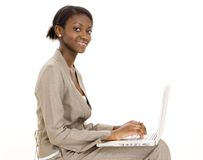 Happy Worker. A happy young black woman using a laptop computer Stock Photography
