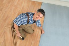 Happy worker assembling new laminate floor. High Angle View Of A Smiling Worker Assembling New Laminate Floor stock photo