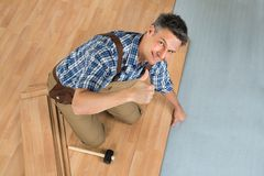 Happy worker assembling new laminate floor. High Angle View Of A Smiling Worker Assembling New Laminate Floor stock photos