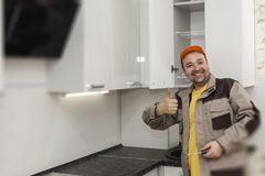 Happy Worker. Assembly Of Kitchen Furniture Royalty Free Stock Photos