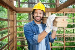Happy Worker Carrying Wooden Planks On Shoulder Royalty Free Stock Photo