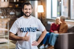 Enthusiastic volunteer looking happy while helping people. Happy worker. Cheerful positive young volunteer looking glad while helping senior people sitting Royalty Free Stock Photos
