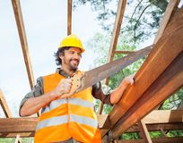 Happy Worker Cutting Wood With Handsaw At Site Stock Photo