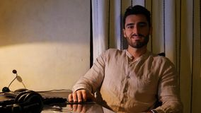 Happy worker at desk at home smiling to camera. Excited or happy attractive young businessman sitting at desk with computer at home smiling to the camera stock image