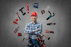 Happy worker handyman  Jack of all trades  or builder with construction tools. Stand and smile, on  grey concrete wall background . Repair service and
