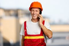 Happy worker in hard hat talking on phone. Stock Image