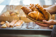 Happy worker holding a basket of croissant Stock Photography