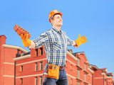 Happy worker holding a brick and spreading arms with a building Stock Photos