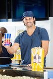 Happy Worker Holding Drink At Cinema Concession Royalty Free Stock Photography